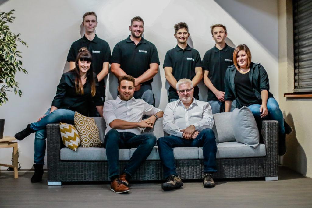 8-Personen-Maenner-und-Frauen-posieren-auf-einem-Sofa-fuer-ein-Mitarbeiter-Bild