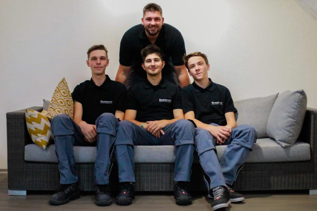 4-maennliche-Auszubildende-posieren-auf-einem-Sofa-fuer-ein-Mitarbeiter-Bild